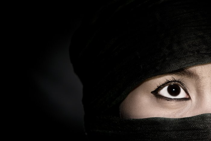 A mysterous close up portrait of a female model in a black head scarf against black background - photography lighting mistakes
