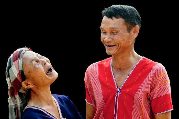 A portrait of a Pwo Karen Couple laughing against a black portarit background - photography lighting mistakes