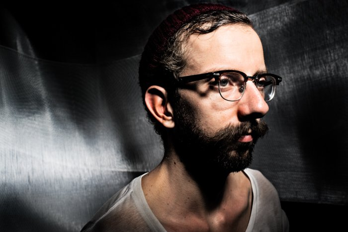 A moody studio portrait of a male model wearing glasses - photography lighting mistakes