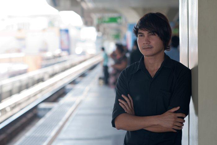 A male model posing Standing on a train platform - photo lighting tips