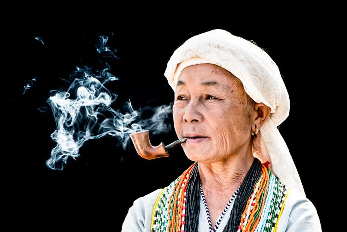 A portrait of a Karen man smoking a pipe against a black background - photography lighting mistakes