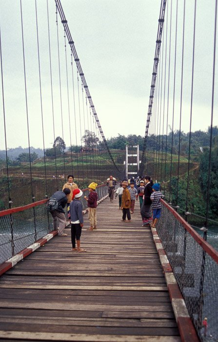 A group of people crossing a wooden bridge