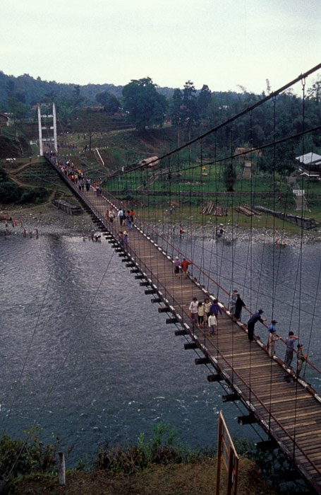 Aerial view of a group of people crossing a wooden bridge