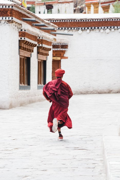 The decisive moment of a young monk running through a street in Ladakh