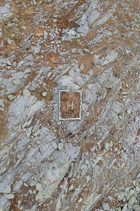 A stunning abstract aerial landscape photography shot of a helicopter landing area on rocky terrain