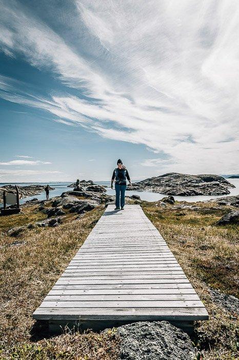 An outdoor photographer walking on a wooden bridge among a beautiful landscape - adventure photography gear