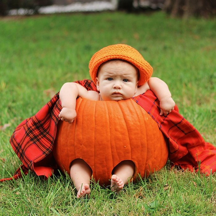 Adorable autumn portrait of a baby in a pumpkin