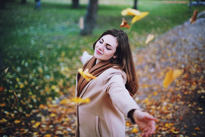 Autumn portrait of a female model throwing leaves in the air.