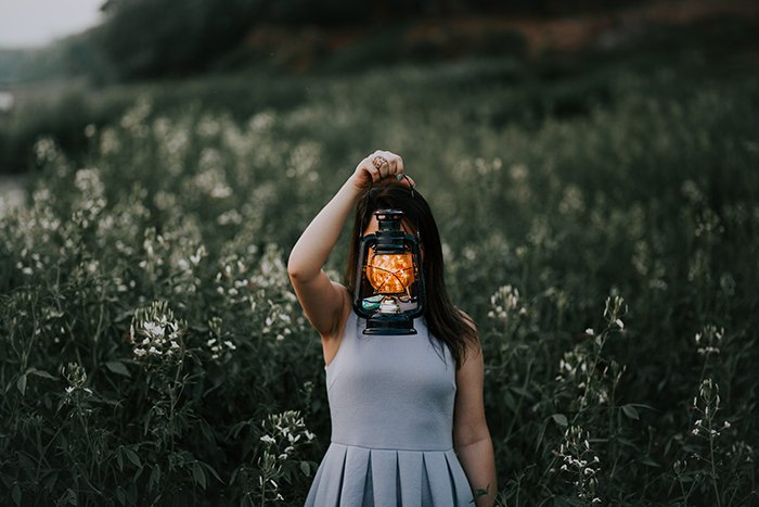 An outdoor portrait of a female holding a lantern with fairy lights in front of her face.