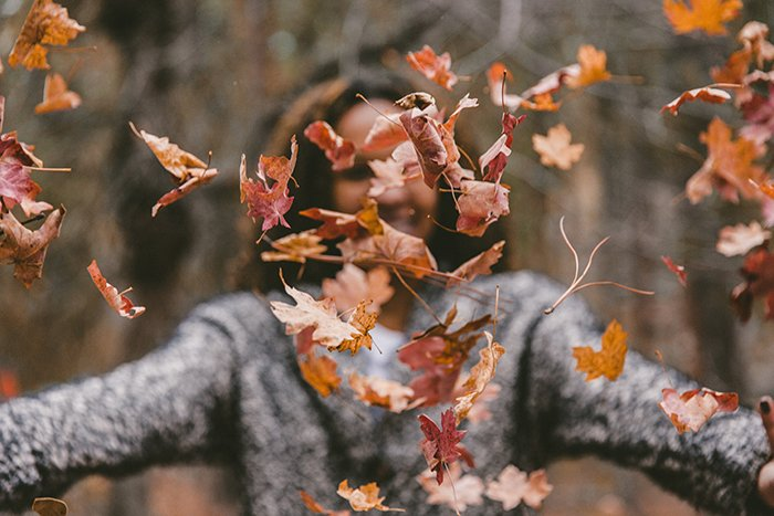 Autumn photography of thrown leaves in the foreground with a blurred female in the background