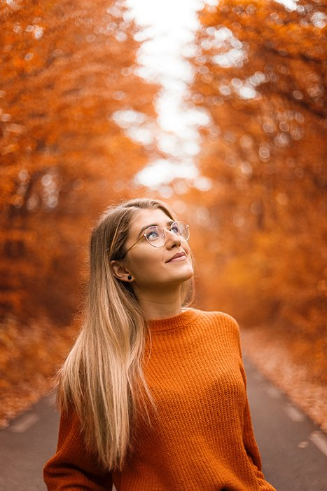 Beautiful autumn photography of a female model in orange posing in front of orange leaved trees