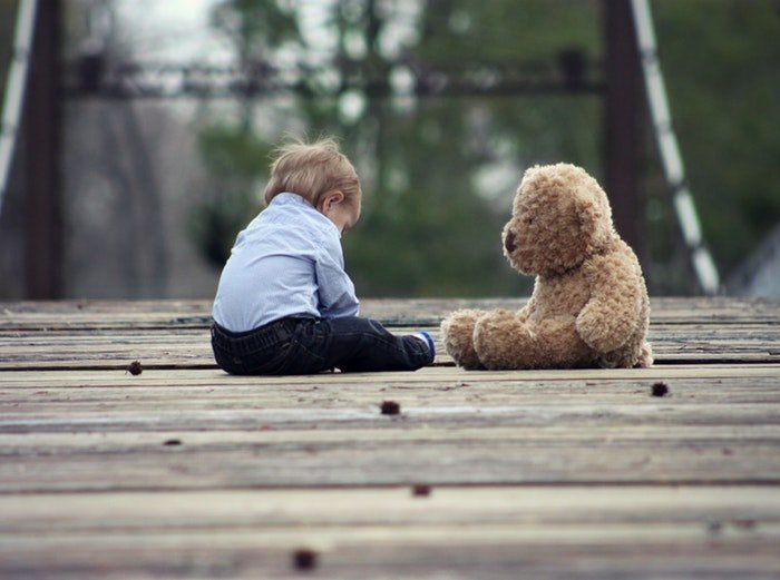 A small child sitting with a teddy bear