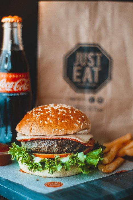 A delicious hamburger beside a softdrink and paper food bag