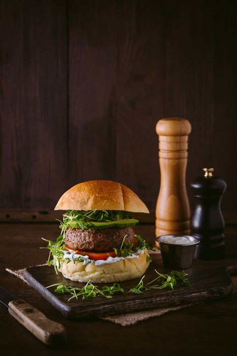 A delicious burger photo setup on rustic board and background