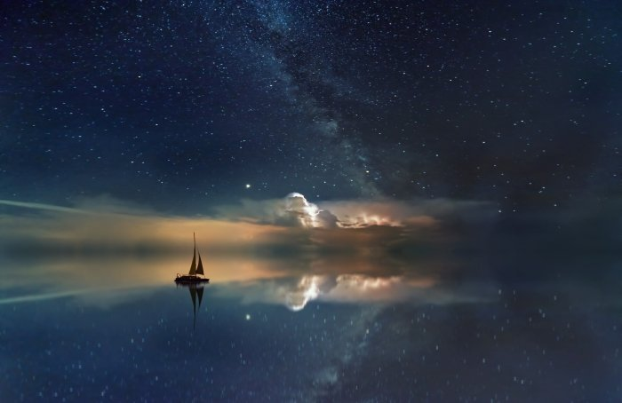 An edited image of a sailboat floating in the sea with a starry sky