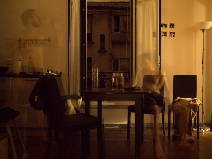 A conceptual photo of a room with a blurred image of a man