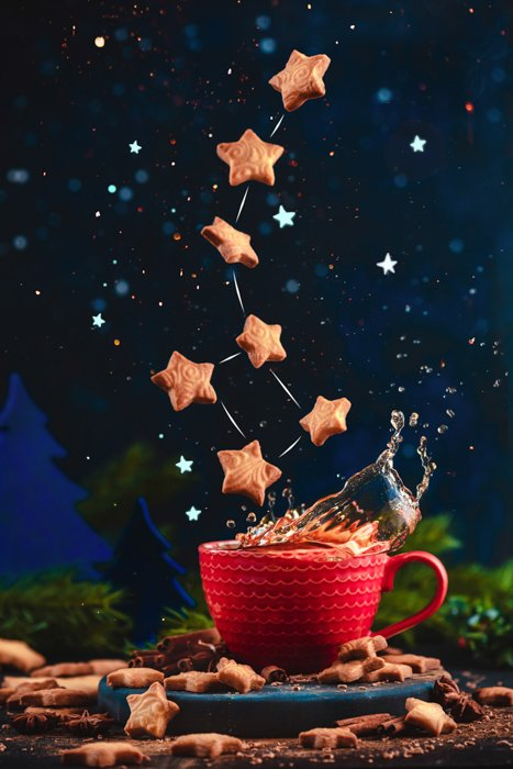 Creative food still life including coffee cups, sugar and flying star shaped cookies