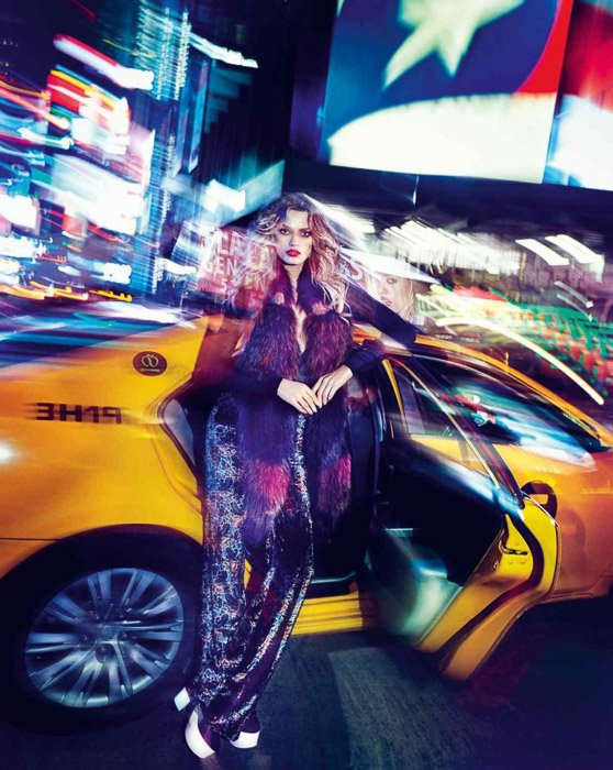 Striking potrrait of a femal fashion model posing by a taxi - outdoor fashion photography at night