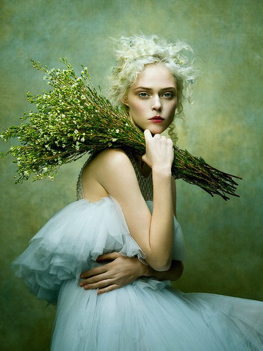 A pictorialist style fashion portarit of a femal model posing against green background
