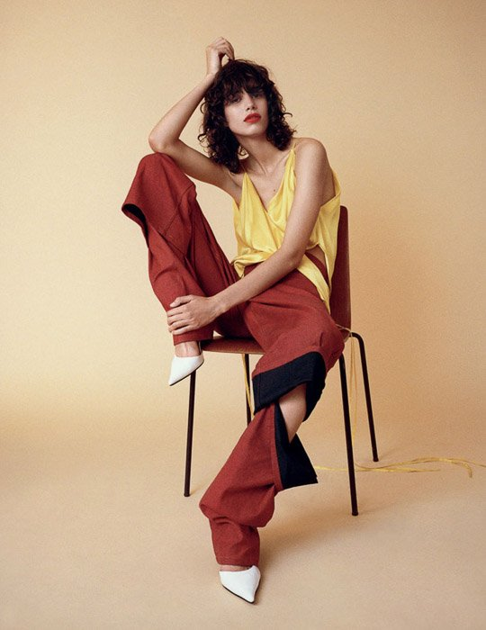 A female model posing on a chair against a pale yellow background - fashion photo inspiration