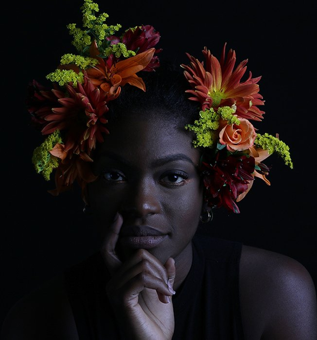 Atmospheric portrait of a female model posing indoors with flowers in her hair - how to photograph the female face