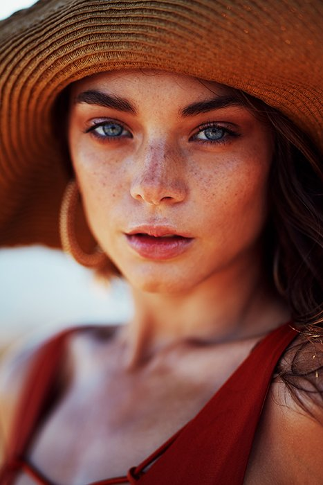 A stunning portrait of a female model in a sunhat - female face portrait