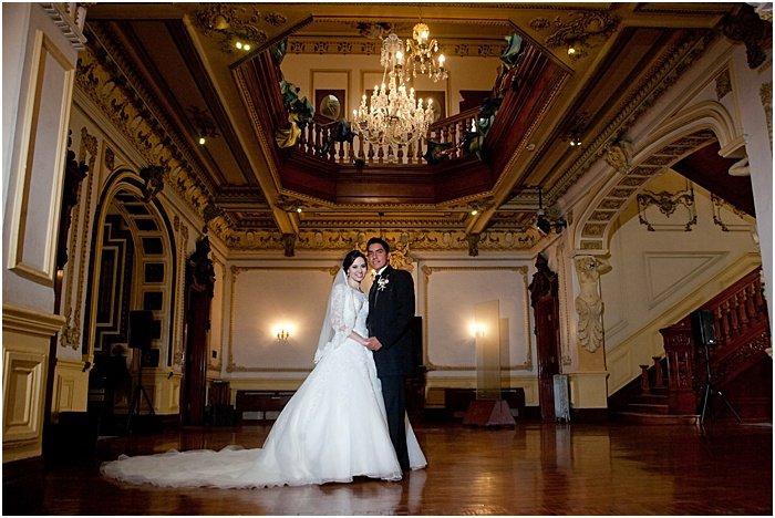 A wedding portrait of a newlywed couple posing in a lavish interior - wedding flash photography