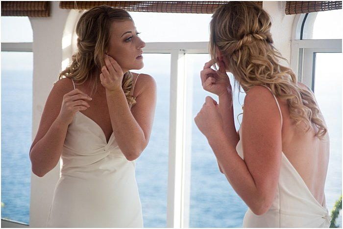 A wedding portrait of a bride fixing her earrings in a mirror - wedding flash photography
