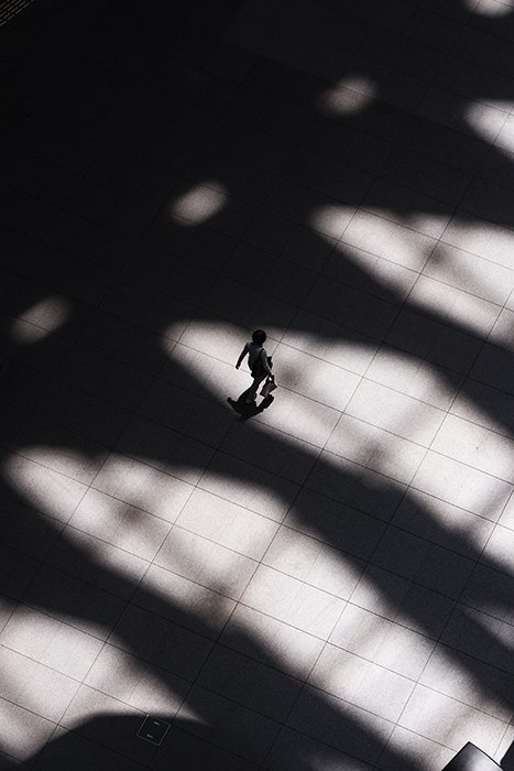 Aerial photo of a person walking among heavy shadows on stone path - form photography