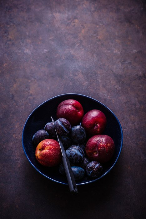 Dark and moody fruit photography of plums in a bowl