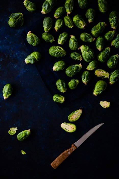 A dark and moody flatlay of Brussels sprouts on dark blue background