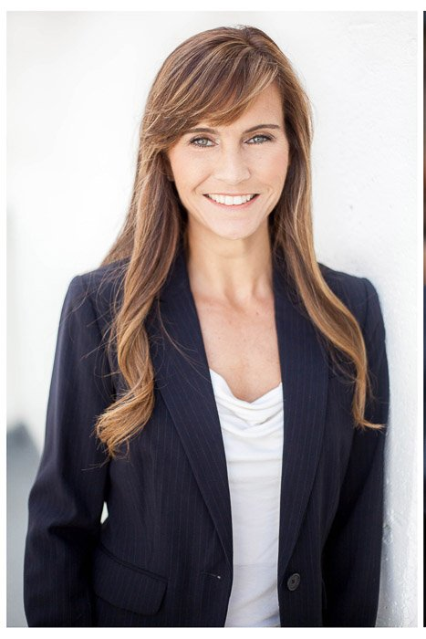 A corporate headshot of a female against a solid wall - headshot background ideas