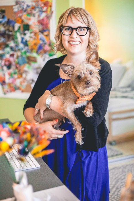 A fun and colorful headshot photo of a woman posing indoors with a small dog