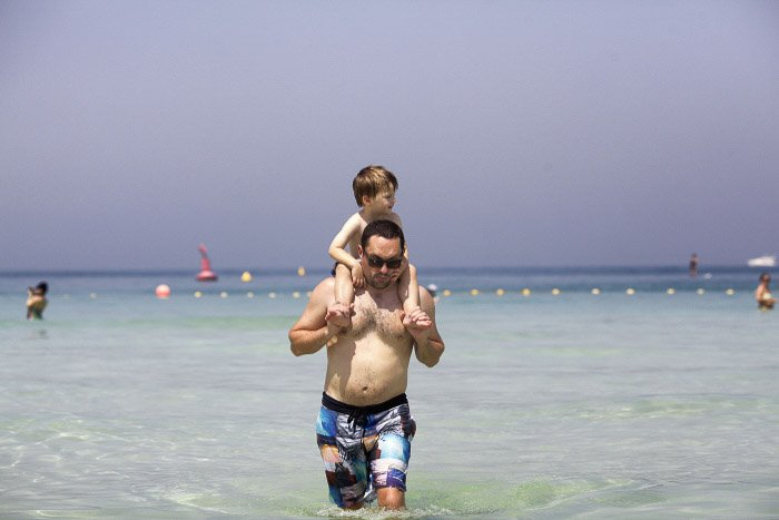 A father and son walking in the ocean