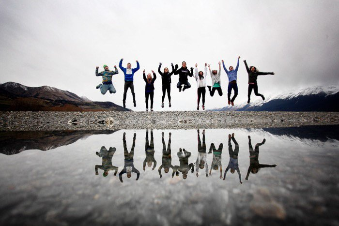A group jumping in front of a body of water
