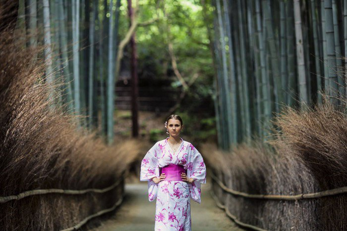 A holiday portrait of a female model in asian style dress posing in a forest
