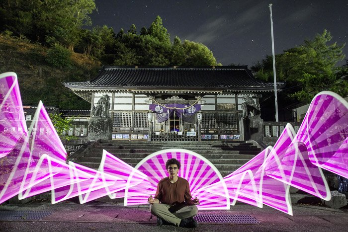 A creative holiday photography portarit of a man sitting cross legged with pink light painting shapes surrounding him