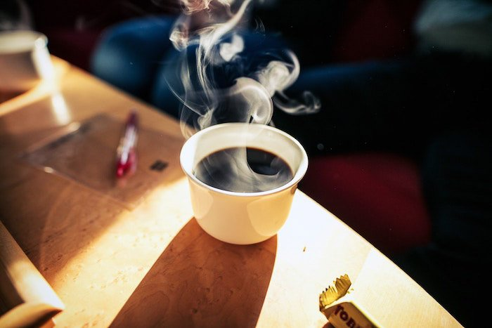 A white cup of hot coffee surrounded by steam- how to photography coffee steam