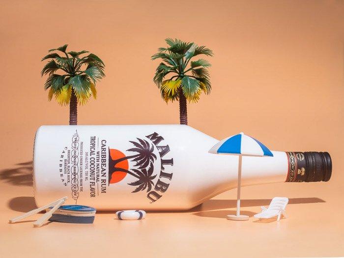 A lifestyle product photography shot of a malibu bottle against an orange background