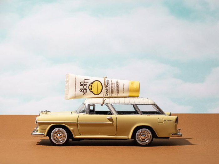 Lifestyle product photography shot featuring a sunscreen bottle on the roof of a miniture car