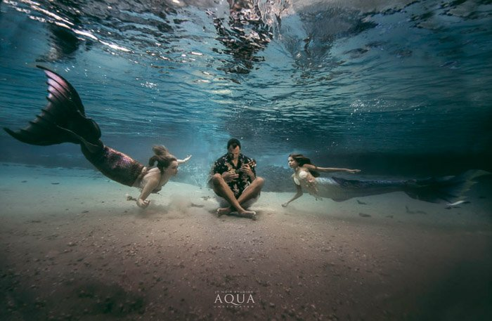 A magical underwater mermaid fantasy scene featuring two mermaids swimming towards an underwater musician - mermaid photoghraphy tips