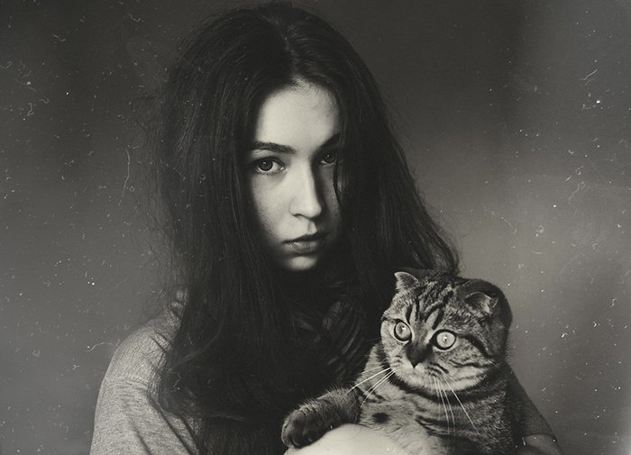 A film noir inspired grainy portrait of a girl holding a cat
