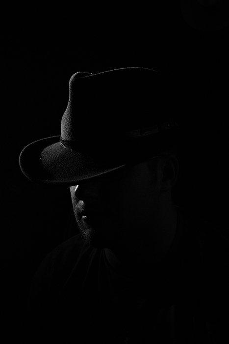 Film noir photography portrait of a male model wearing a cowboy hat