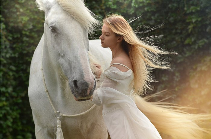 A dreamy photo of a female model with long blond hair posing beside a white horse after using Photoshop overlays