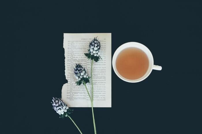 Photo of a piece of paper with a flower and a cup of tea next to it