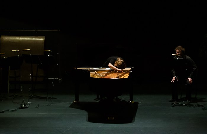 A stage photography shot of a musician playing piano onstage