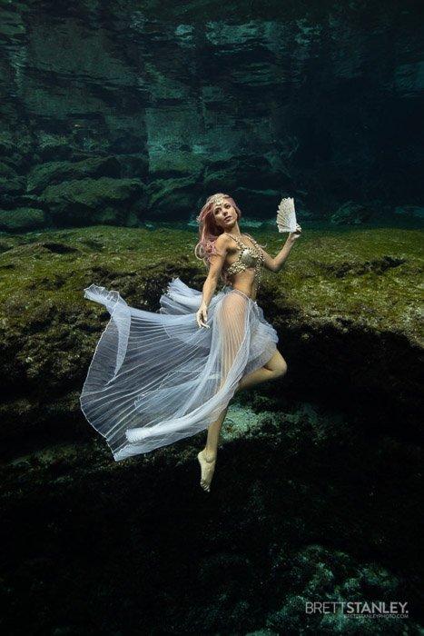 Dreamy underwater portrait of a female model swimming