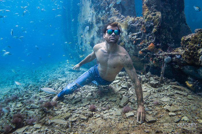 Atmospheric underwater ocean picture of a male model swimming under the water