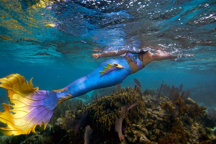 Dreamy underwater portrait of a female model with brightly colored mermaid tail