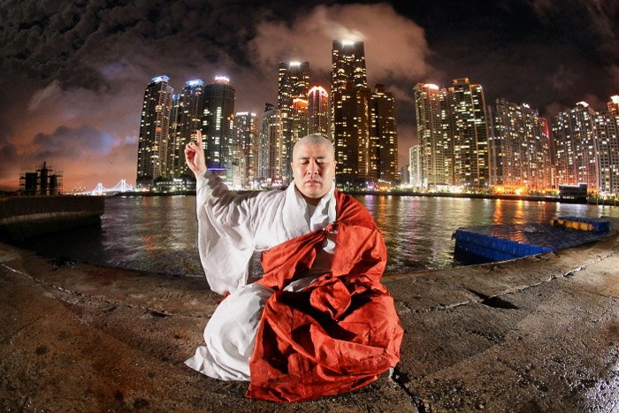 Conceptual urban portrait of a monk meditating in front of a night cityscape